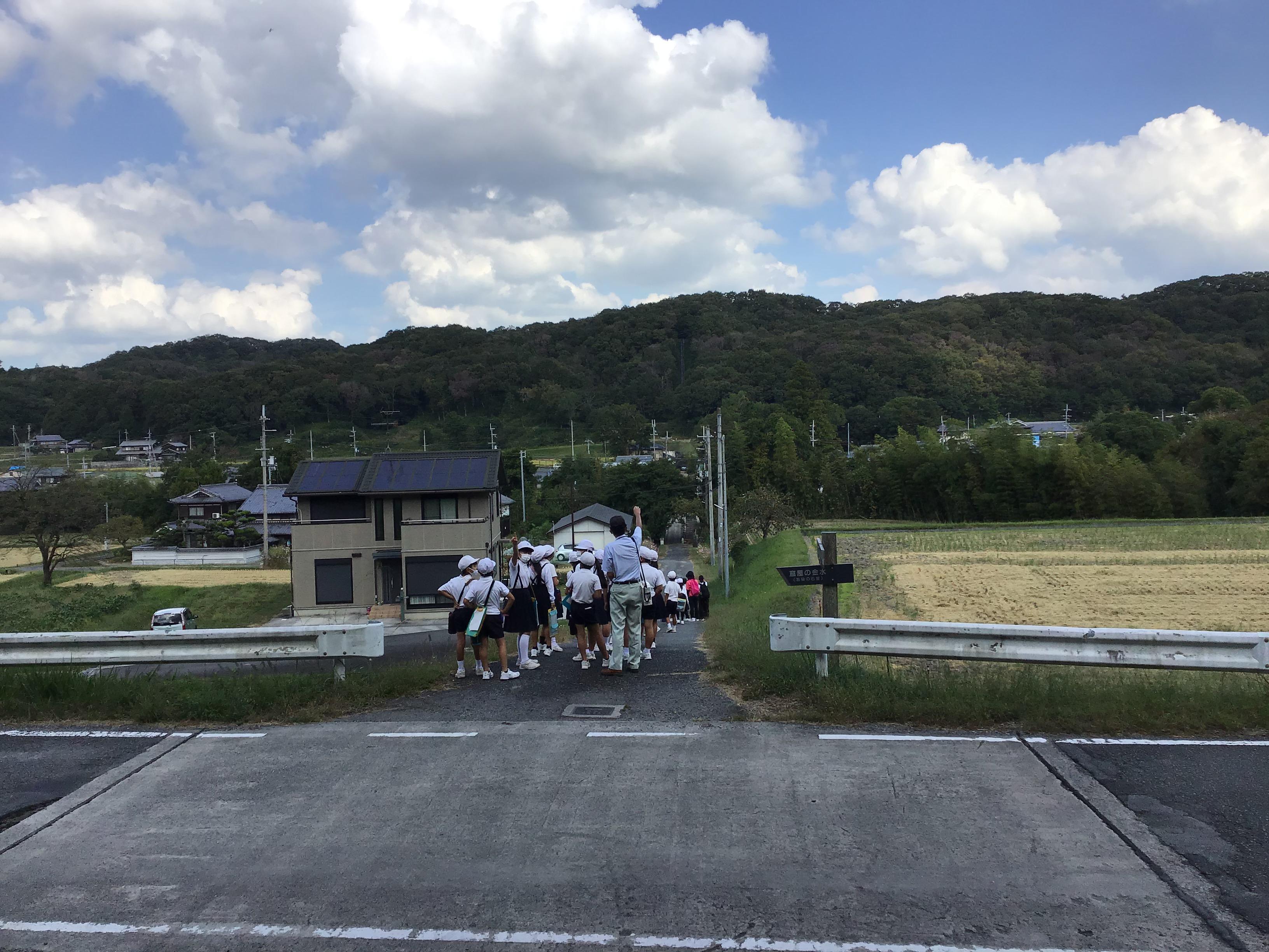 御坂サイフォンの水管橋を渡り切り後ろを振り返って上流の水の飲み口を指さす藤田参事。