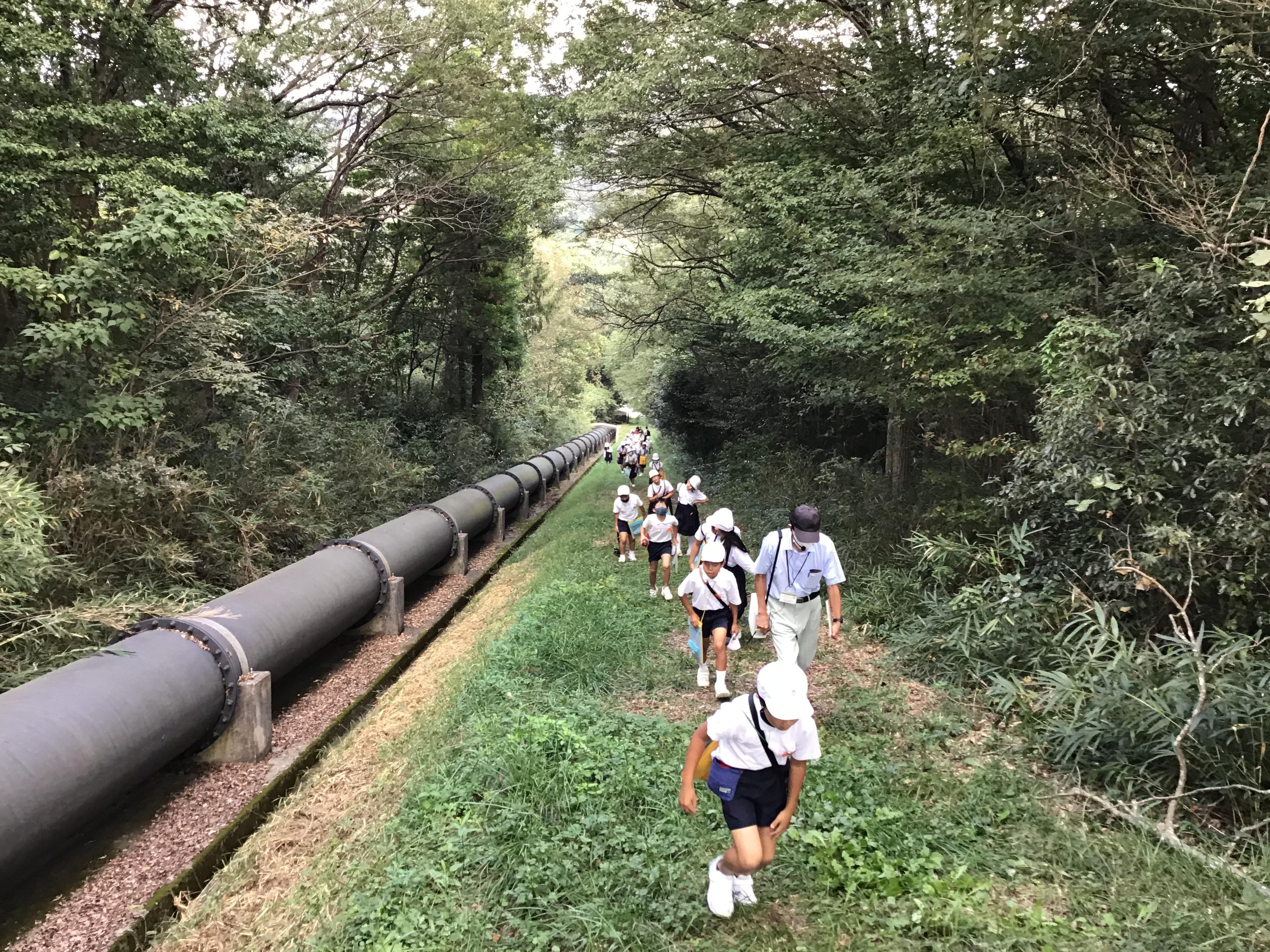 御坂サイフォンの水道管に沿って登ってくる児童たち。走っている子供も。無限の体力があるね。