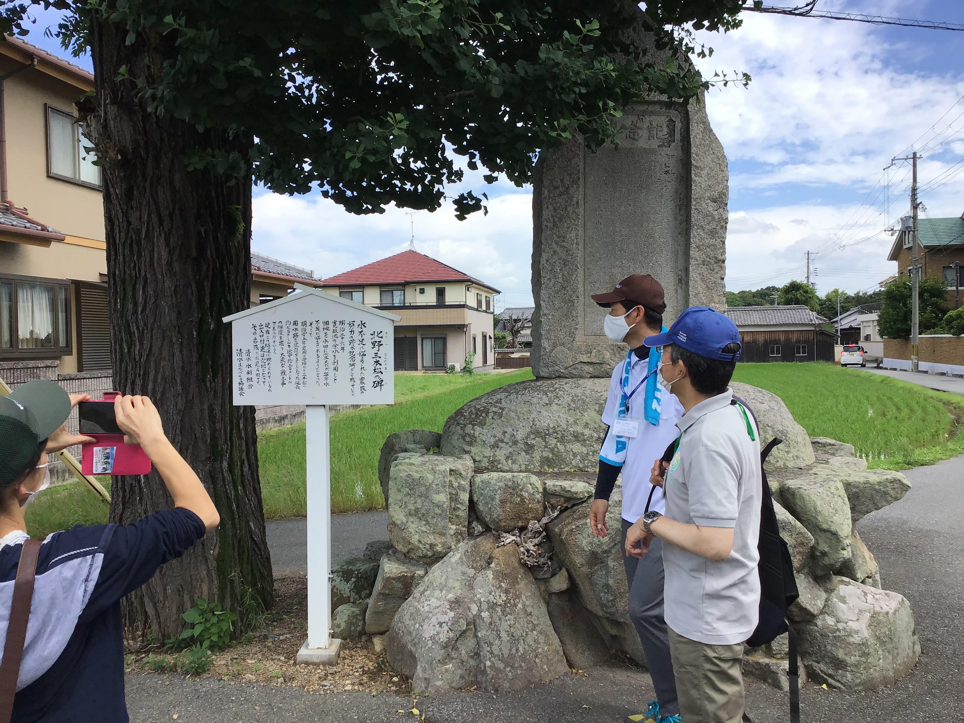 途中、北野三本松の碑を通る。加古川流域土地改良事務所の森脇所長(手前)と東播磨県民局県民課の長谷坂班長(向こう)が水不足に悩まされた農民の努力の跡の碑を見入る。