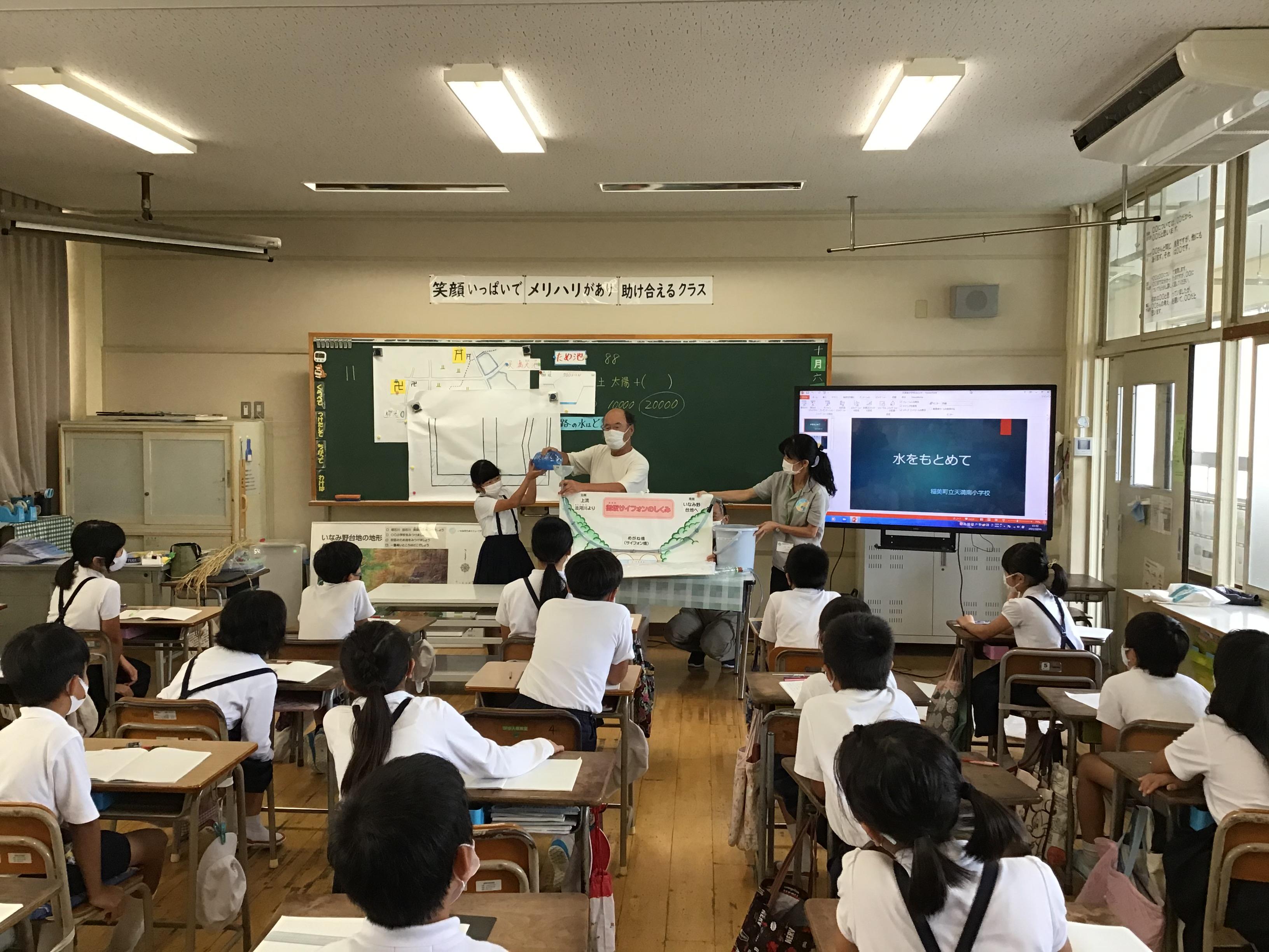 内田先生が児童に順番に御坂サイフォンに見立てた模型に青い水を入れて実際に水が遡上するか確認。