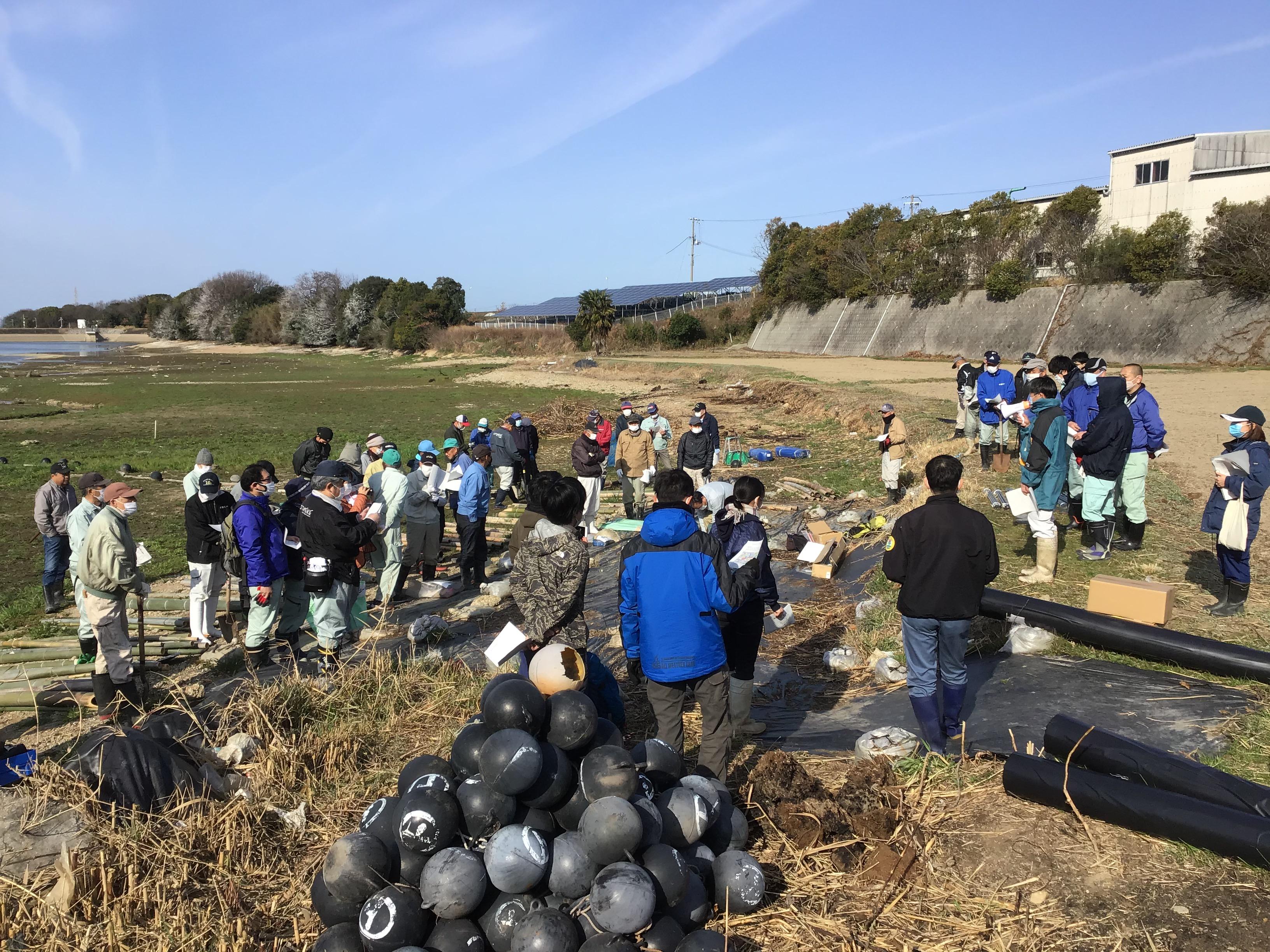 エコロジー研究所の丸井代表の駆除内容説明。手前の黒い球体は猟師さんの網に付ける丸ブイを浮きに使用