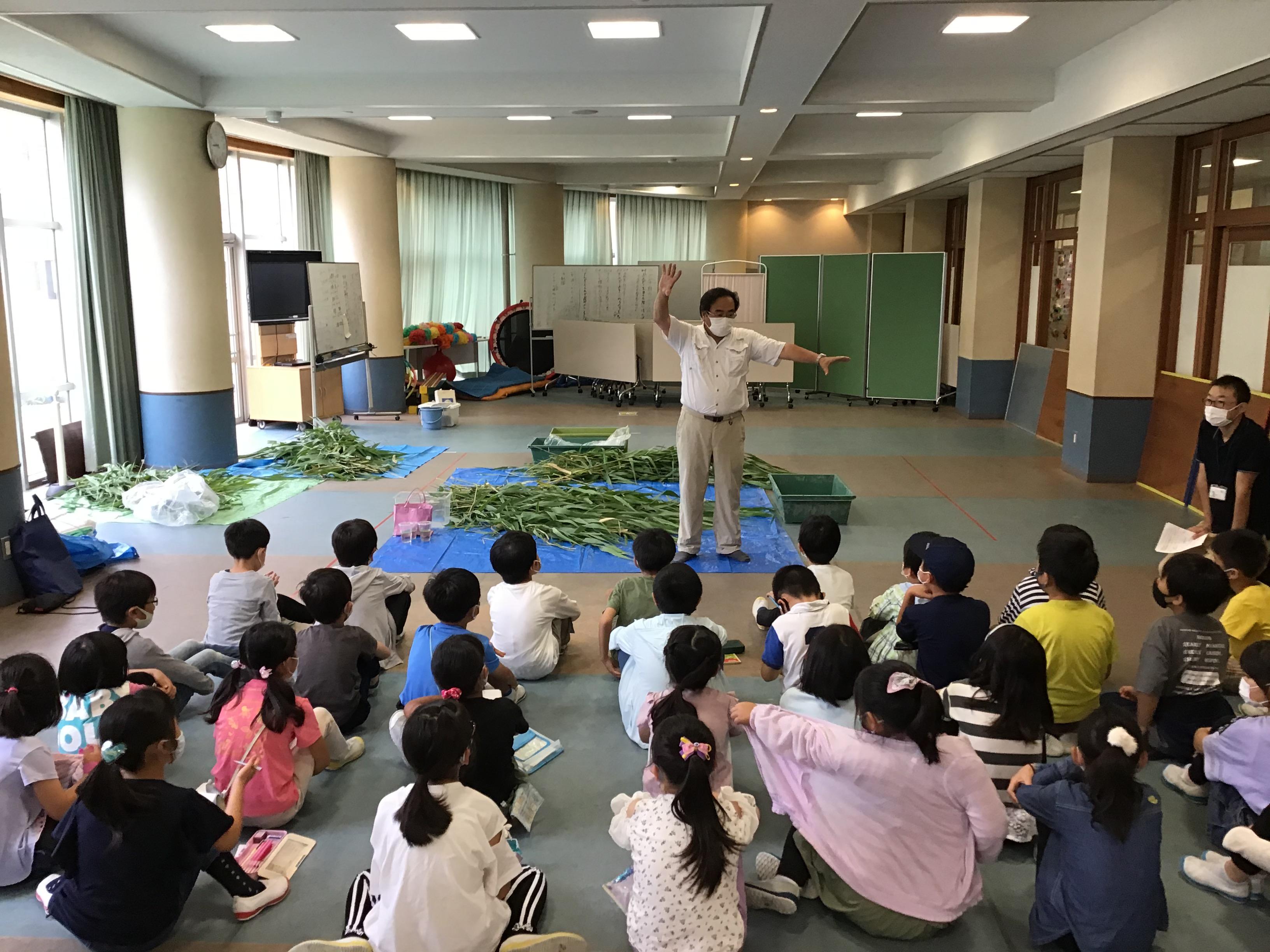 碓井先生がため池の植物について説明(足元の葦は、その後、子供たちが葦笛作りで大はしゃぎ\(^o^)/)吹けなかった子は残念。