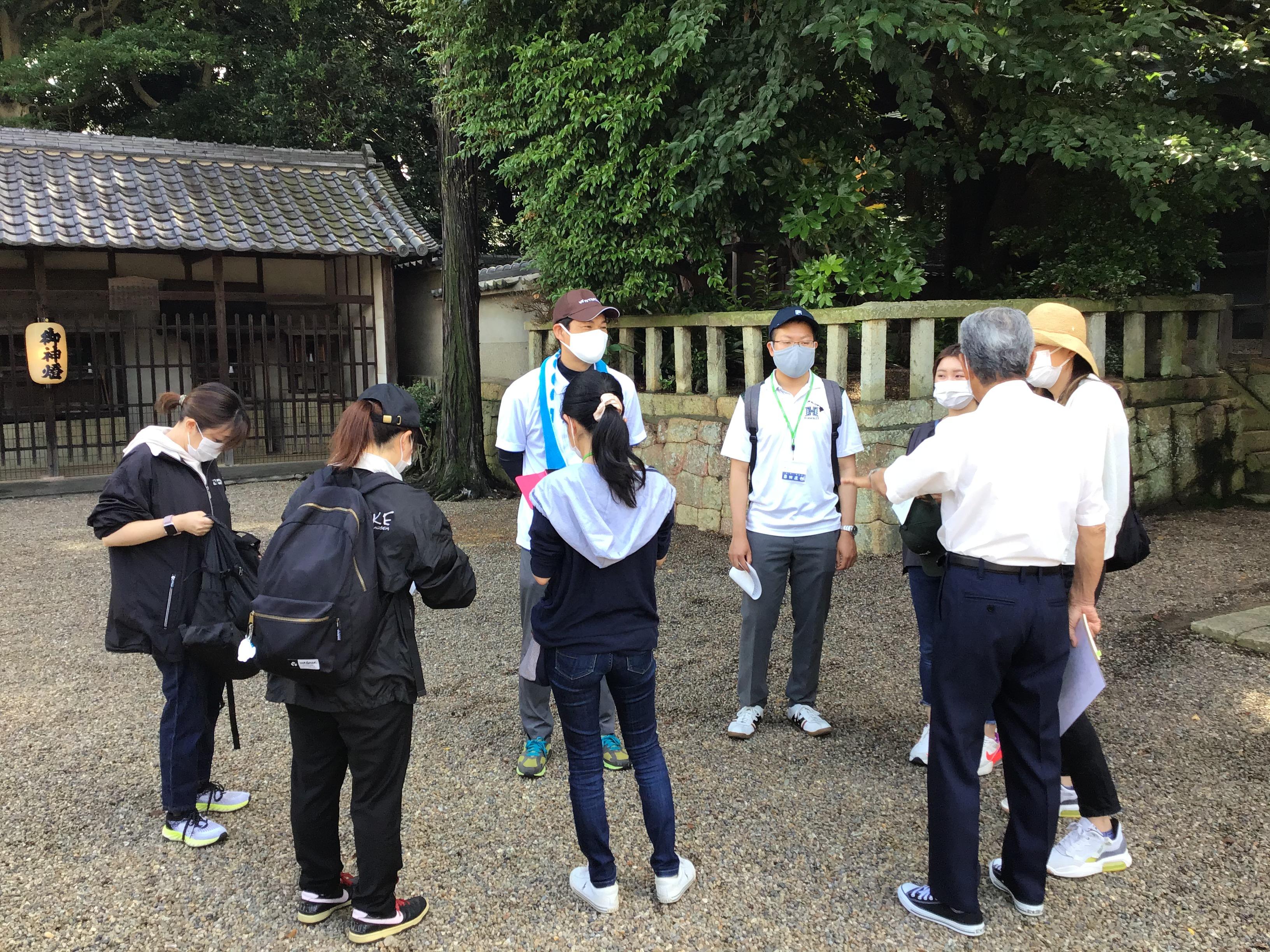 出発前の清水神社で清水ため池協議会の榎本達夫会長(右側背中)から説明を受ける東播磨県民局と北播磨県民局の職員の面々