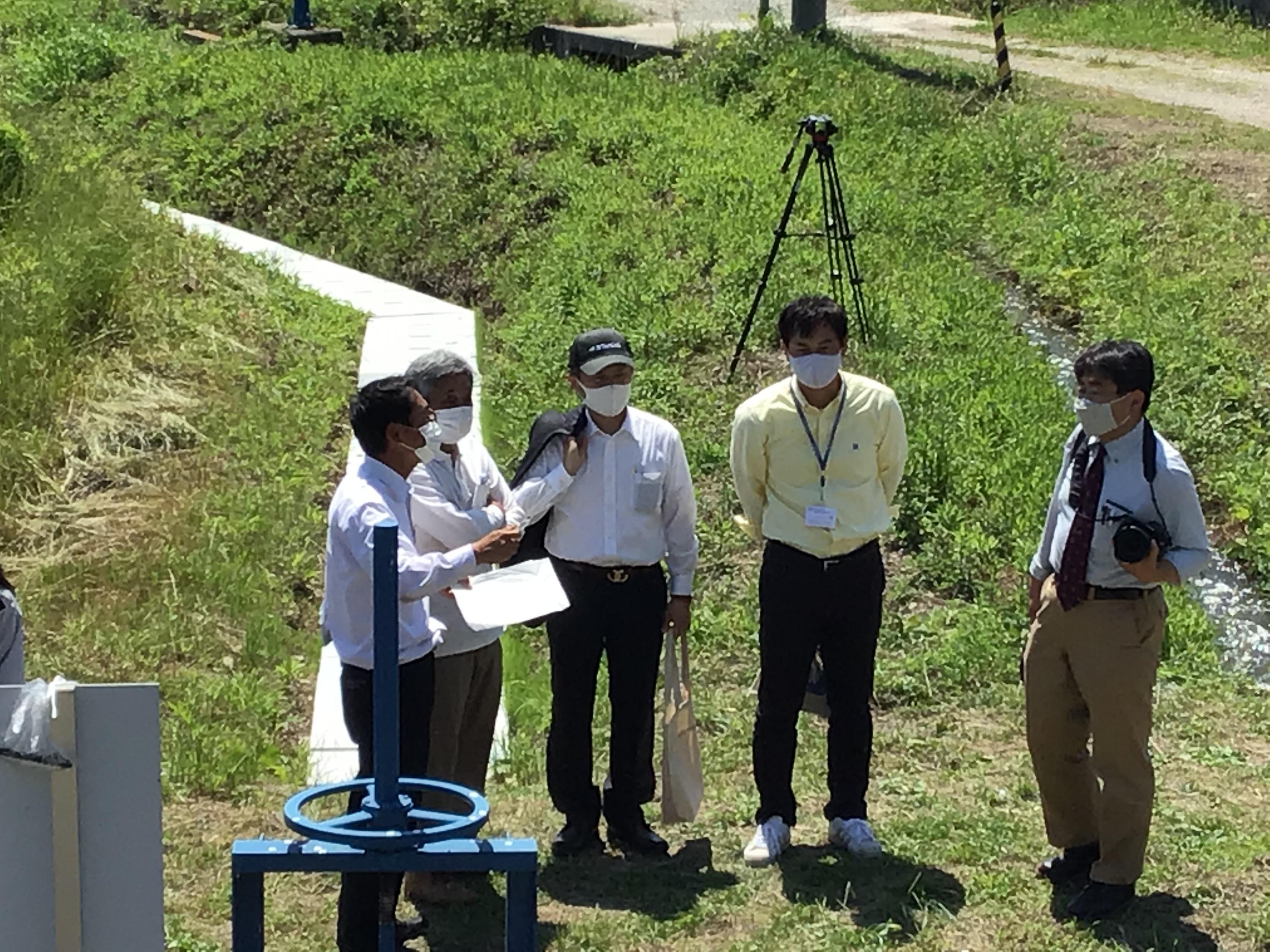 左から二人目の原地域づくり協議会の北本代表から大池の説明を受ける東播磨県民局の小川局長(中央)と水辺地域づくり担当の長谷坂班長(右から二人目)