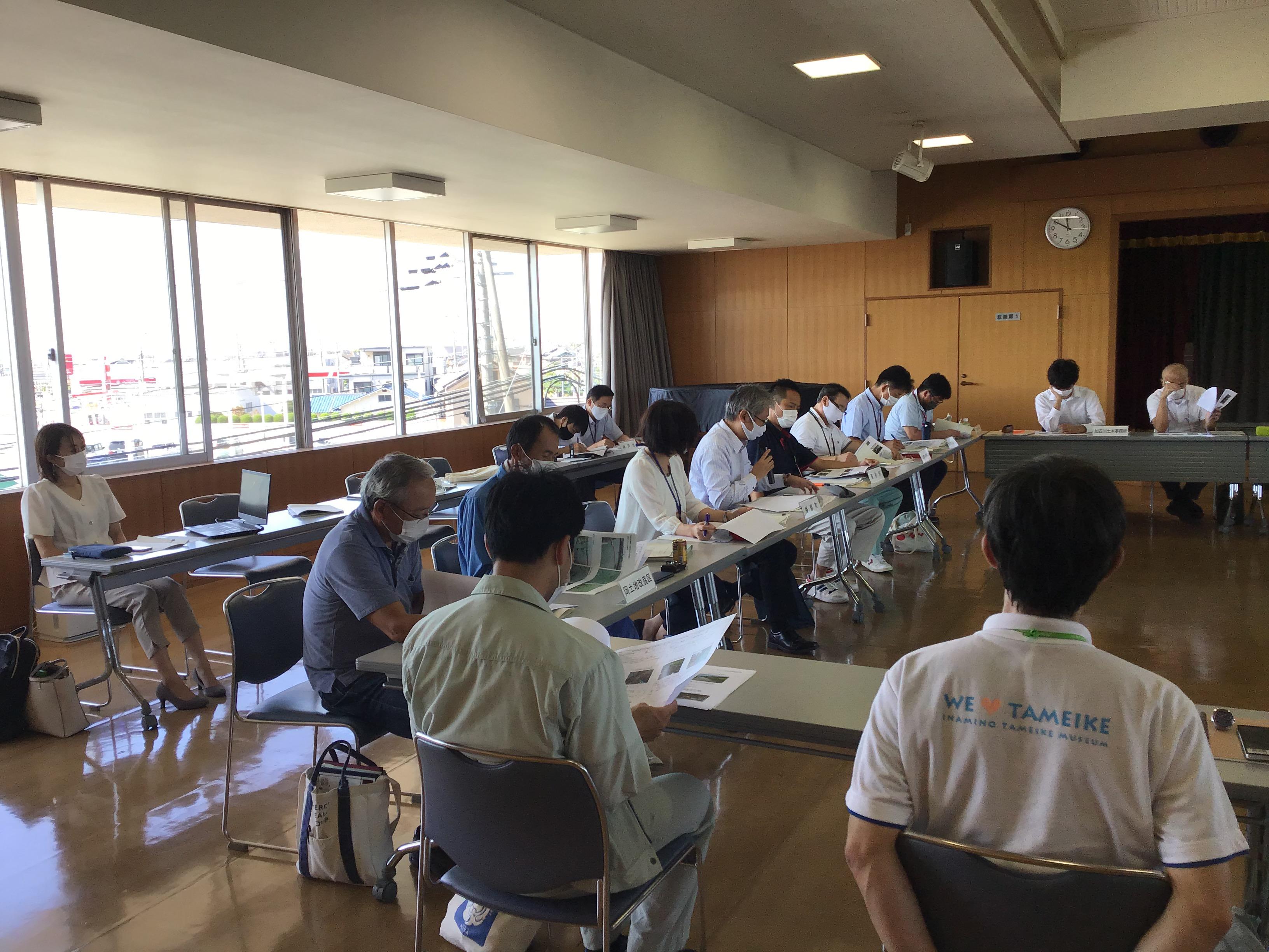喜瀬川のナガエ状況について説明される北山リーダー補佐(写真中央:白カッターシャツの方)