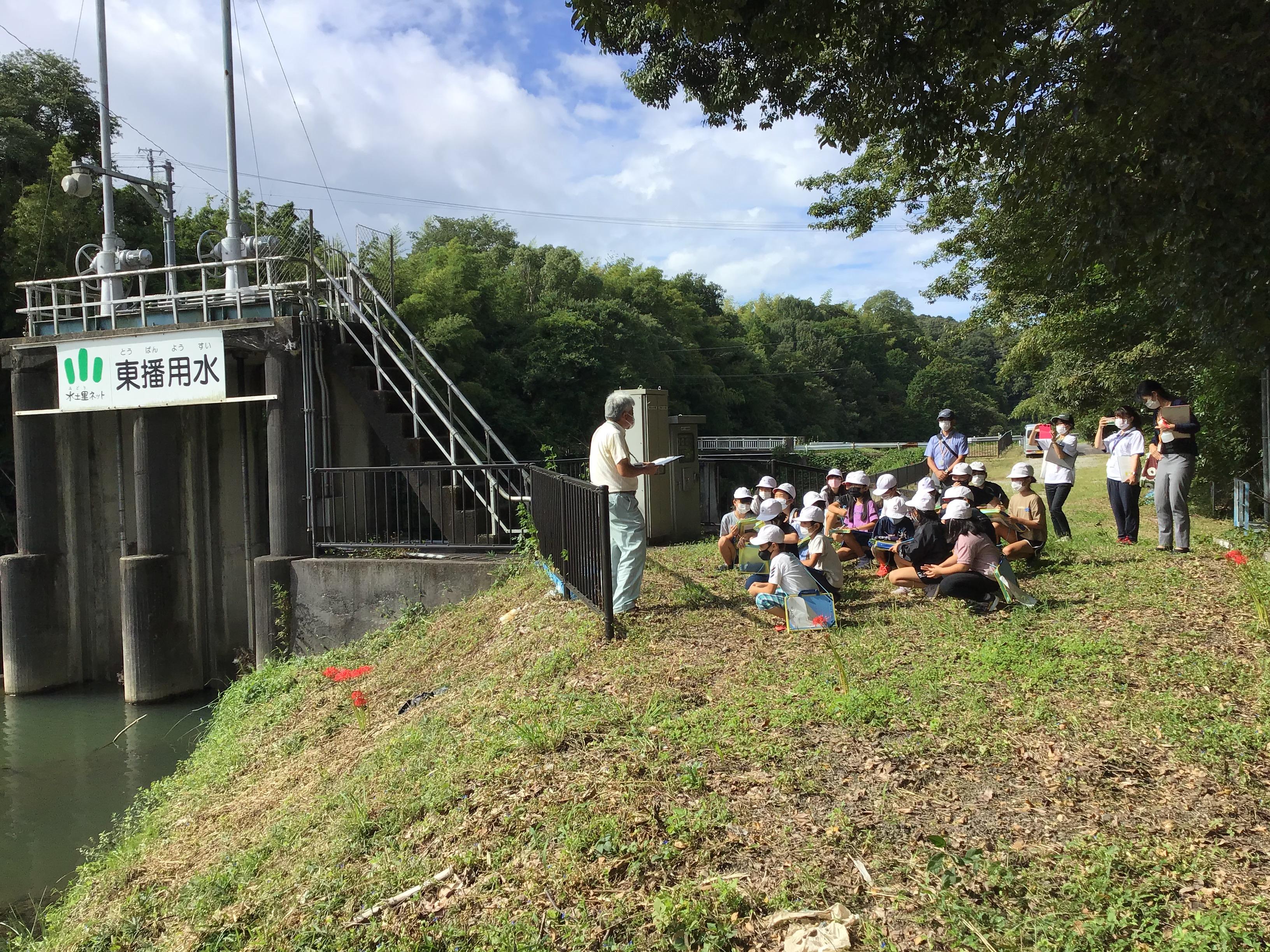 淡河川頭首工で大橋参事が説明。写真左の監視カメラで遠隔操作でゲートの上下が可能。(到着に20分かかってしまうそうです。)