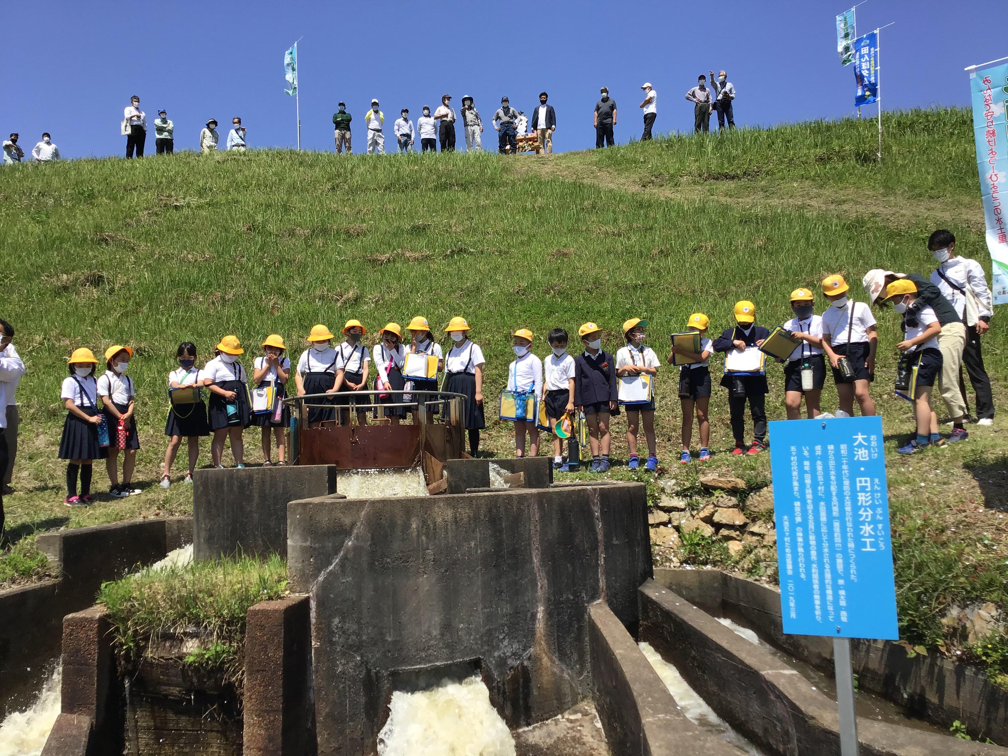 円形分水工からの湧き出る水を確認する志方西小学校の生徒たち