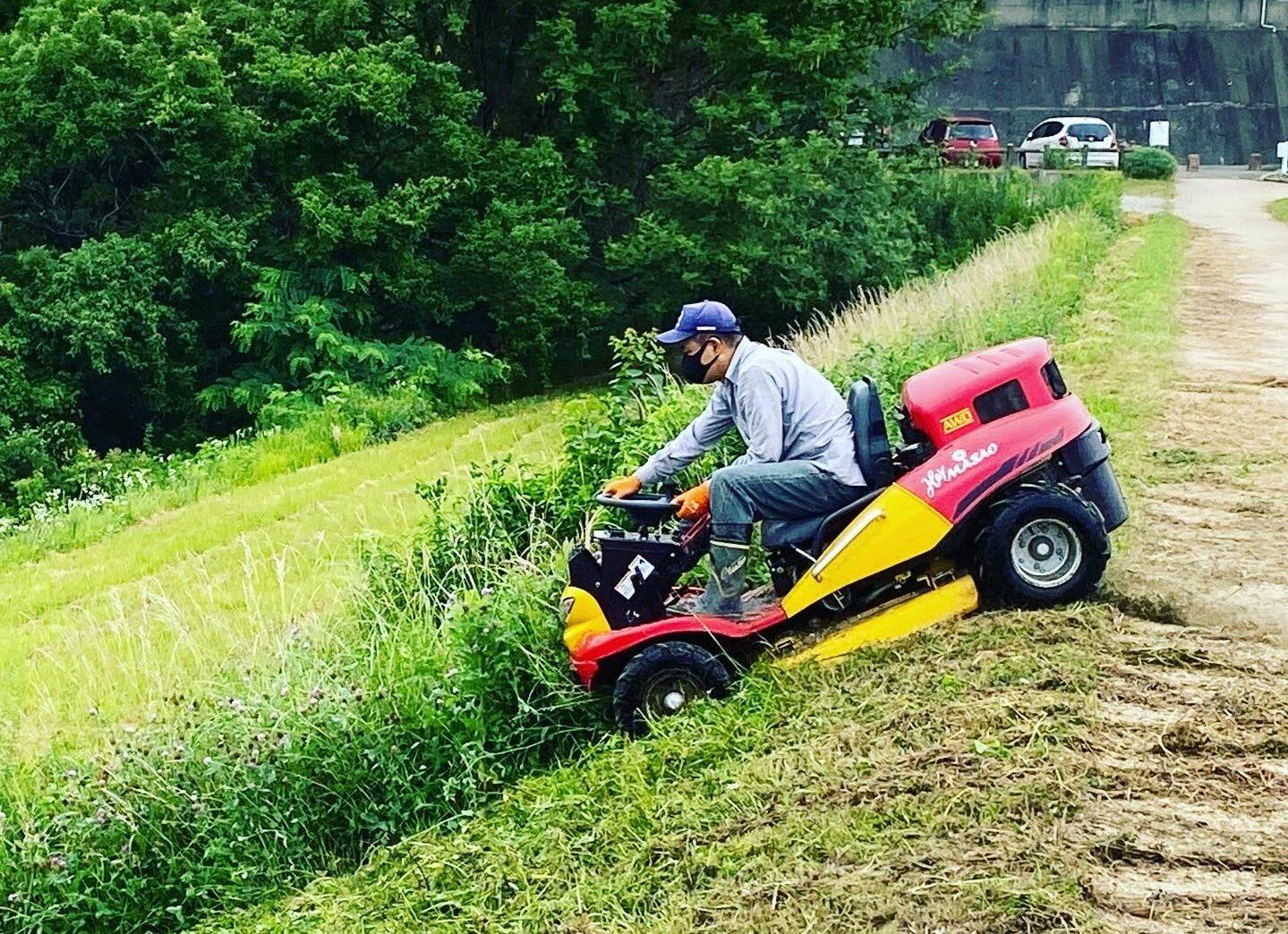 写真のミニカーのような車🚗 これは草刈機です。かなりの急斜面を運転しています!乗りこなすには運転技術がいりそうですね。