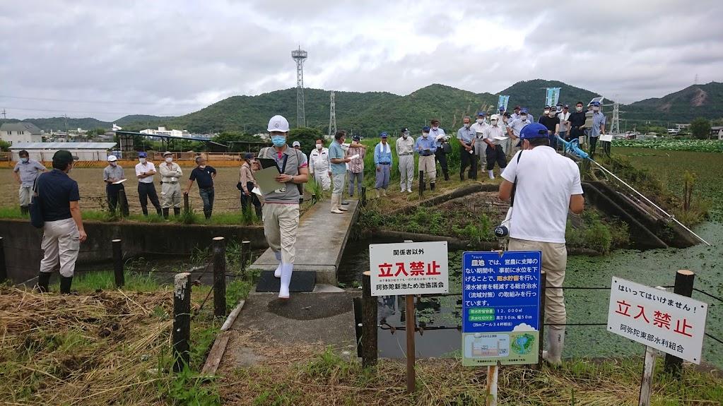 皿池の洪水吐口付近で切欠け(25mプール34杯分)による雨水貯留の説明状況