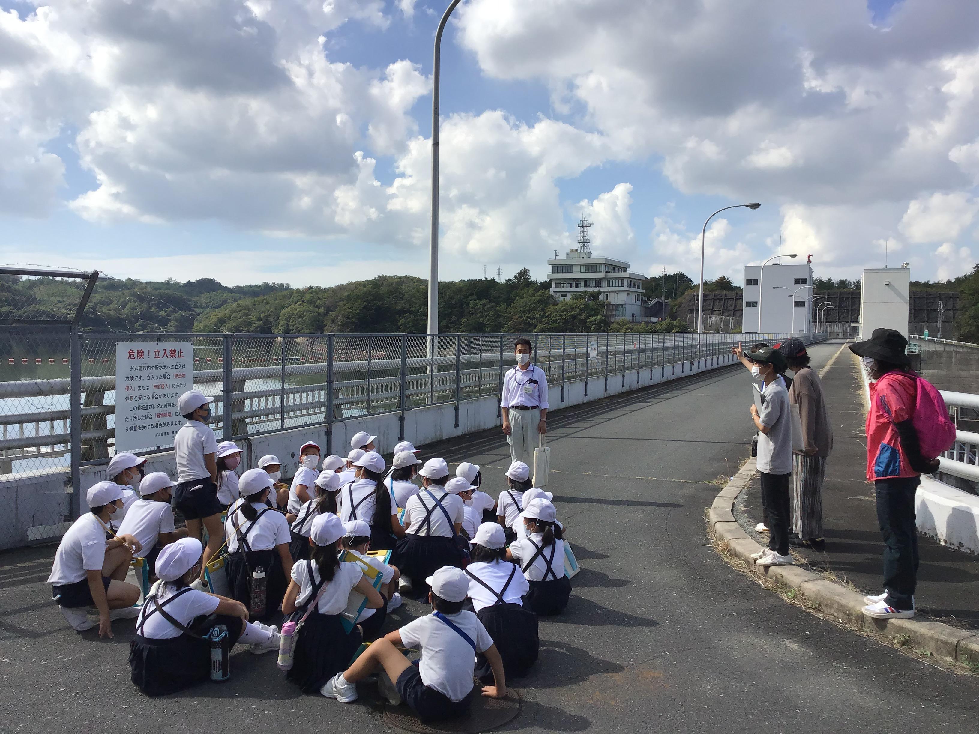吞吐ダム 説明をして頂いた福森所長(中央こちら向き)にお礼を言う児童。奥の建物がダム管理棟。