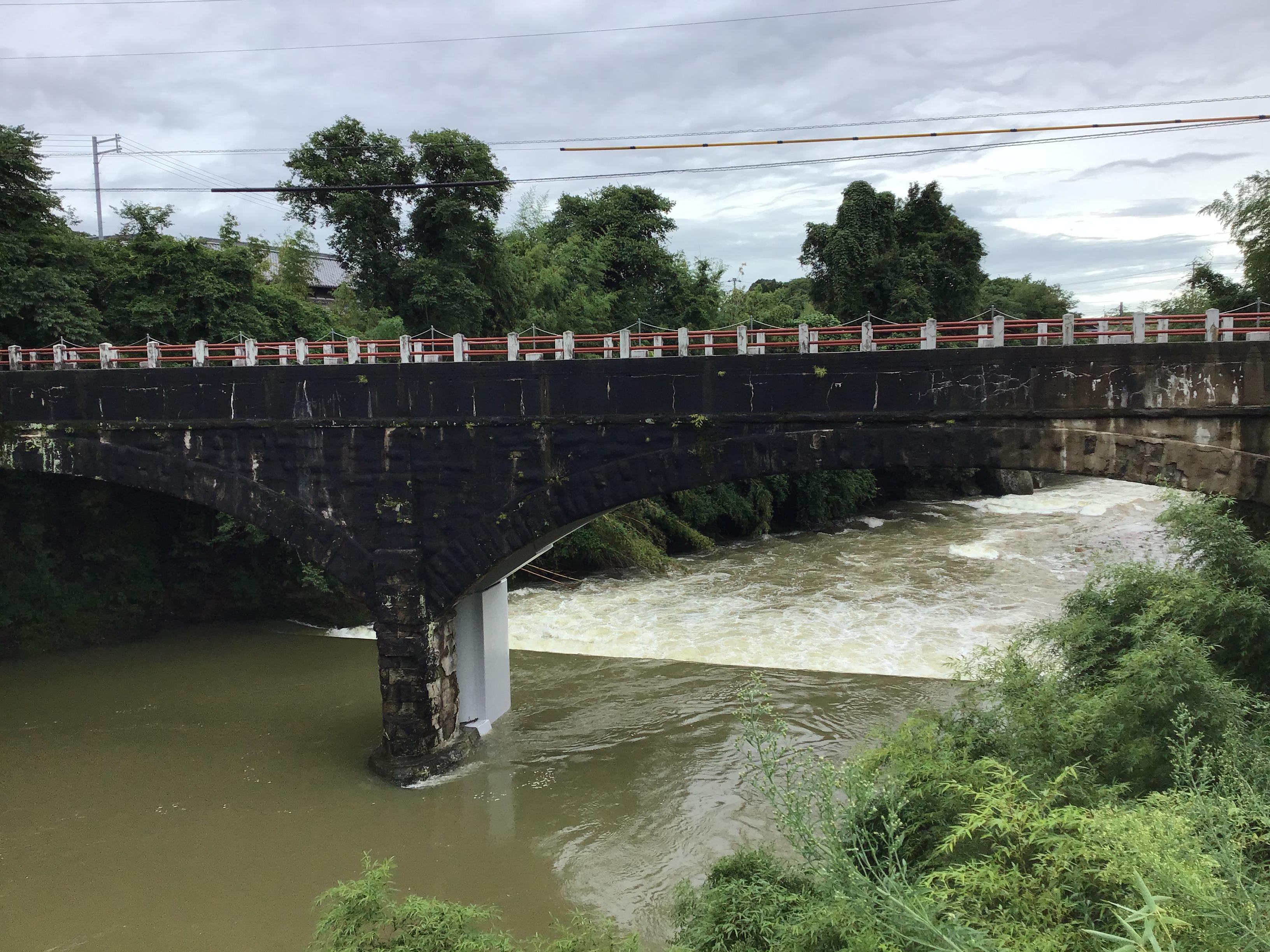 御坂サイフォンの水路橋(サテライト)。後ろに白っぽい橋脚が見えますが今年6月に耐震工事が完成した新しい橋脚です。晴れた日に水面と合わせて眼鏡橋と呼ばれています。この日は大雨で濁流が。下流側の沈下橋も埋没寸前。