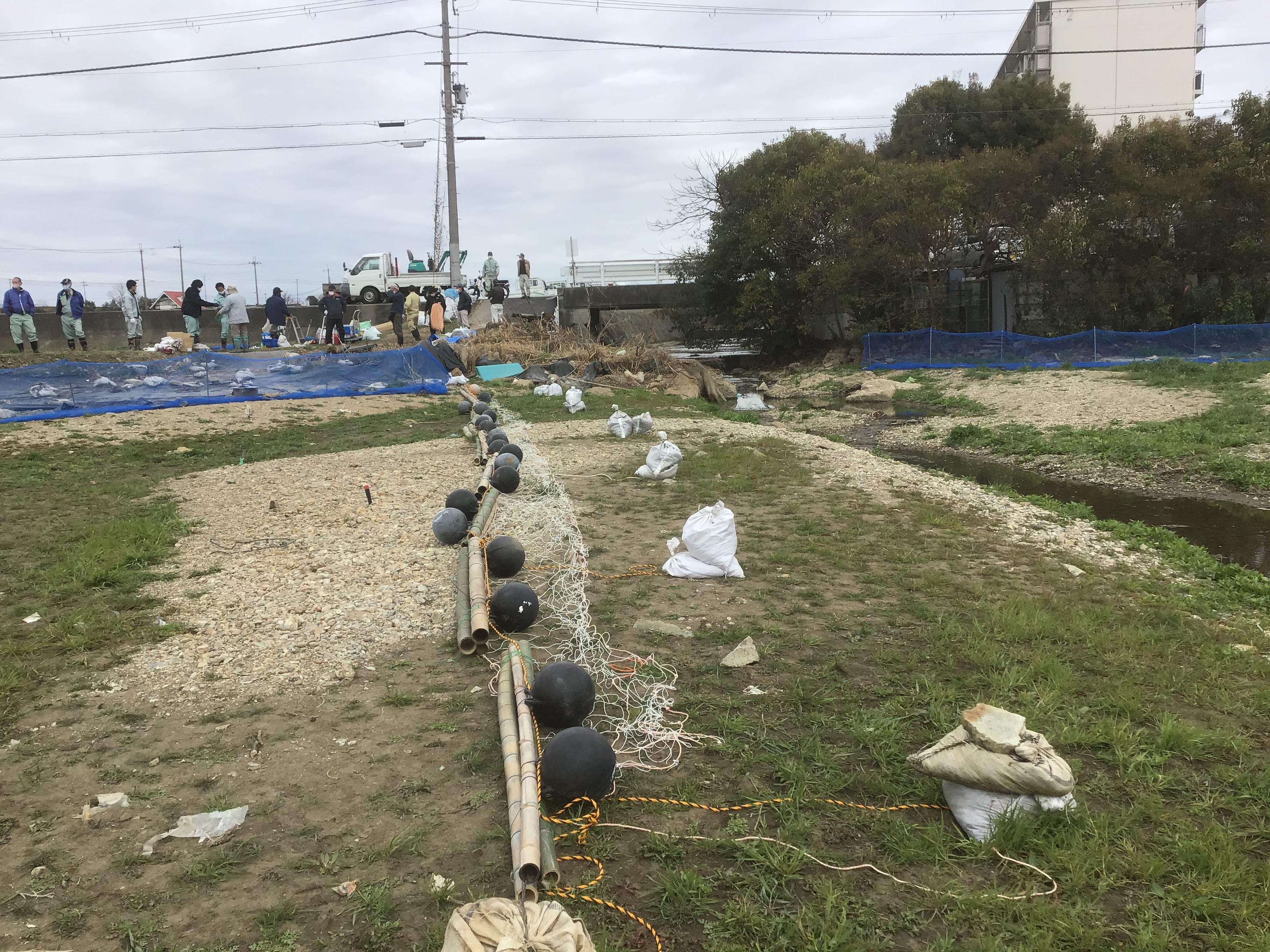 広がりを防ぐネットフェンス。ワンスパン(竹3本と丸ブイ2個)をつないで100m以上設置。